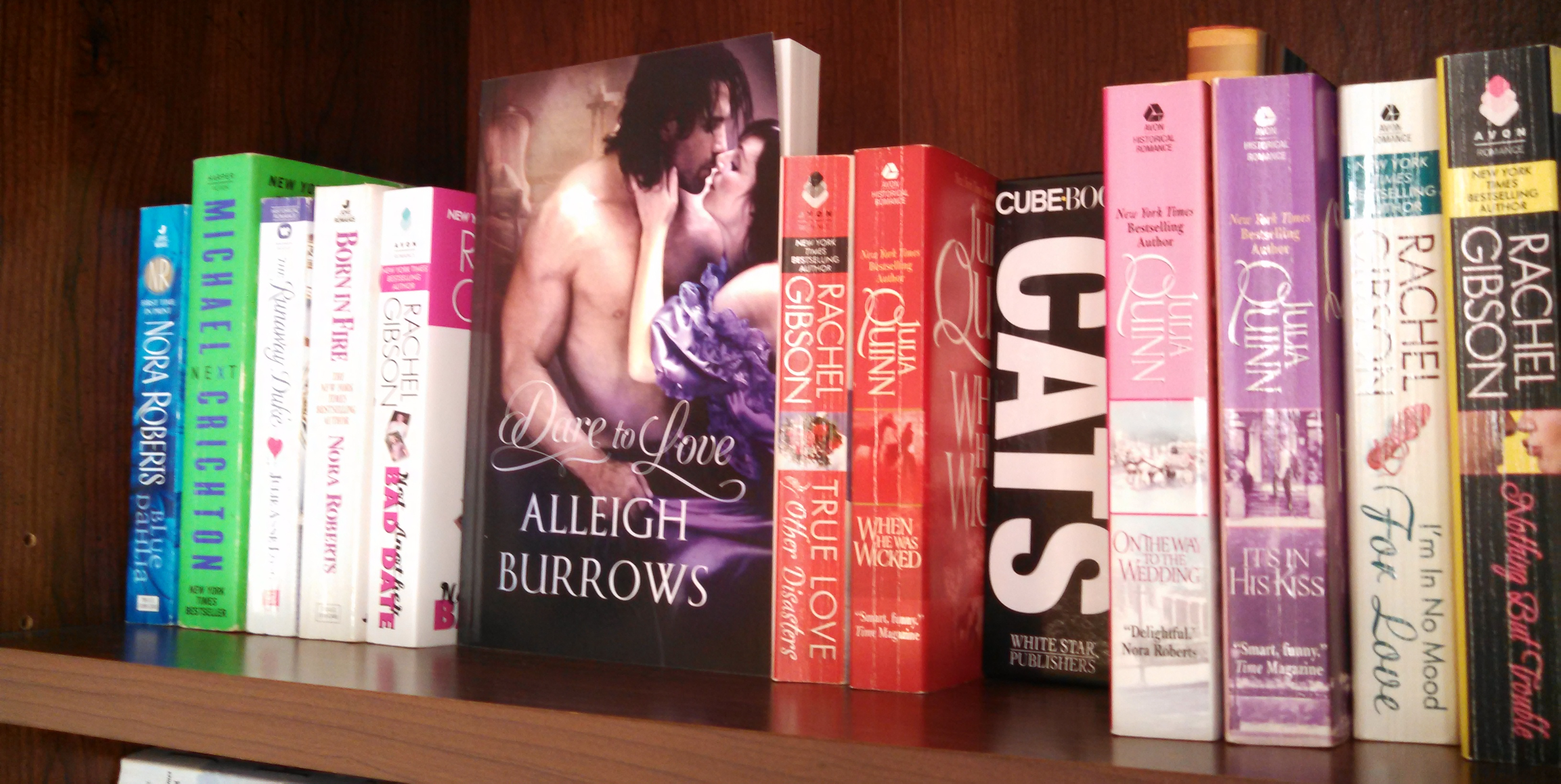 Romance novels and a book of Cats on Alleigh Burrows bookshelf